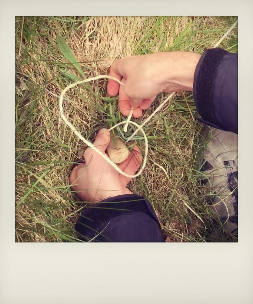 Hands tying a knot around a tent peg