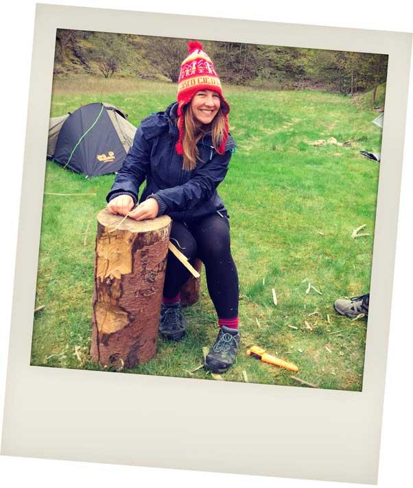 Helen sitting on a tree stump weaving rope
