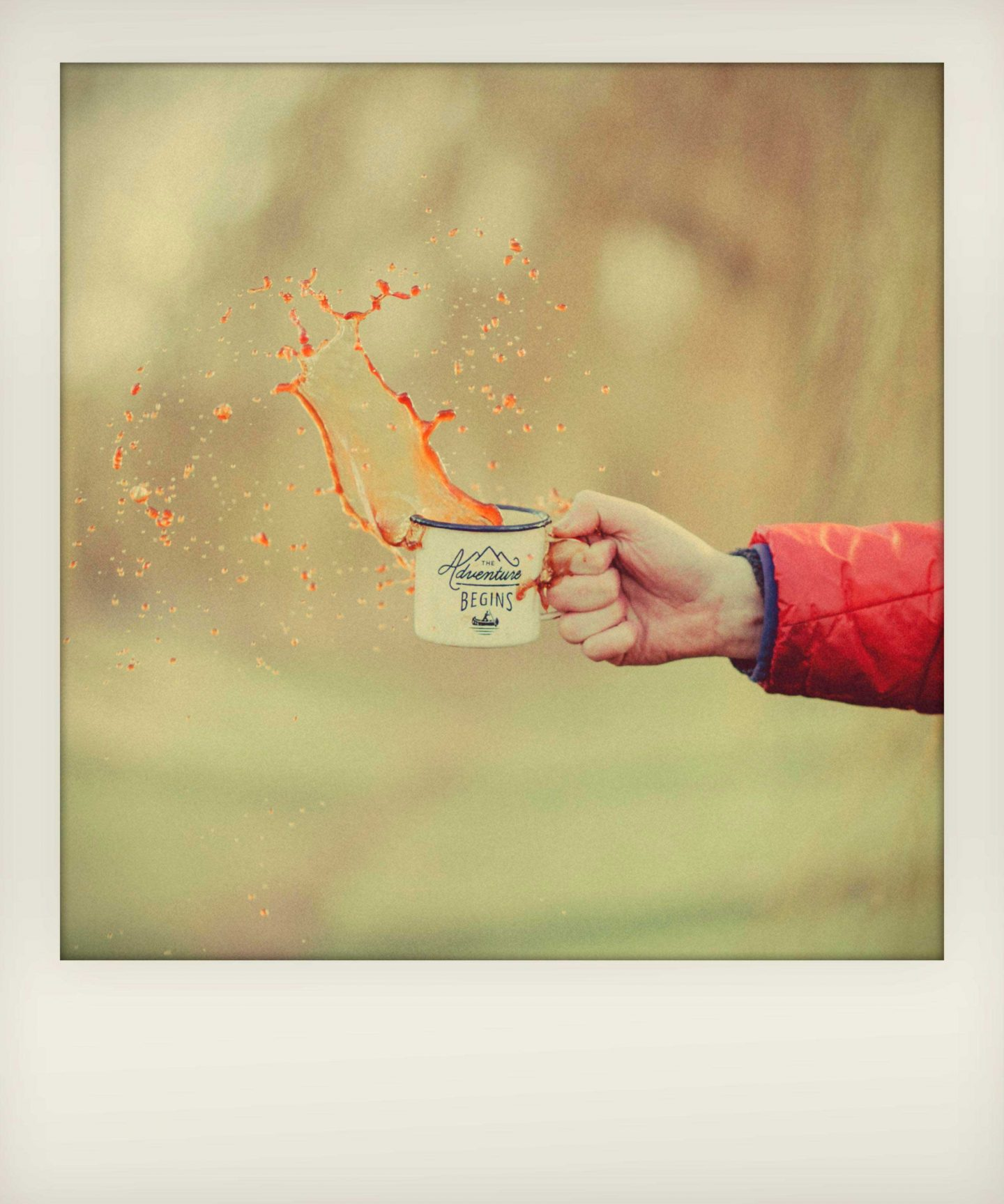 hand holding a spilling cup withthe words 'the adventure begins' written on it