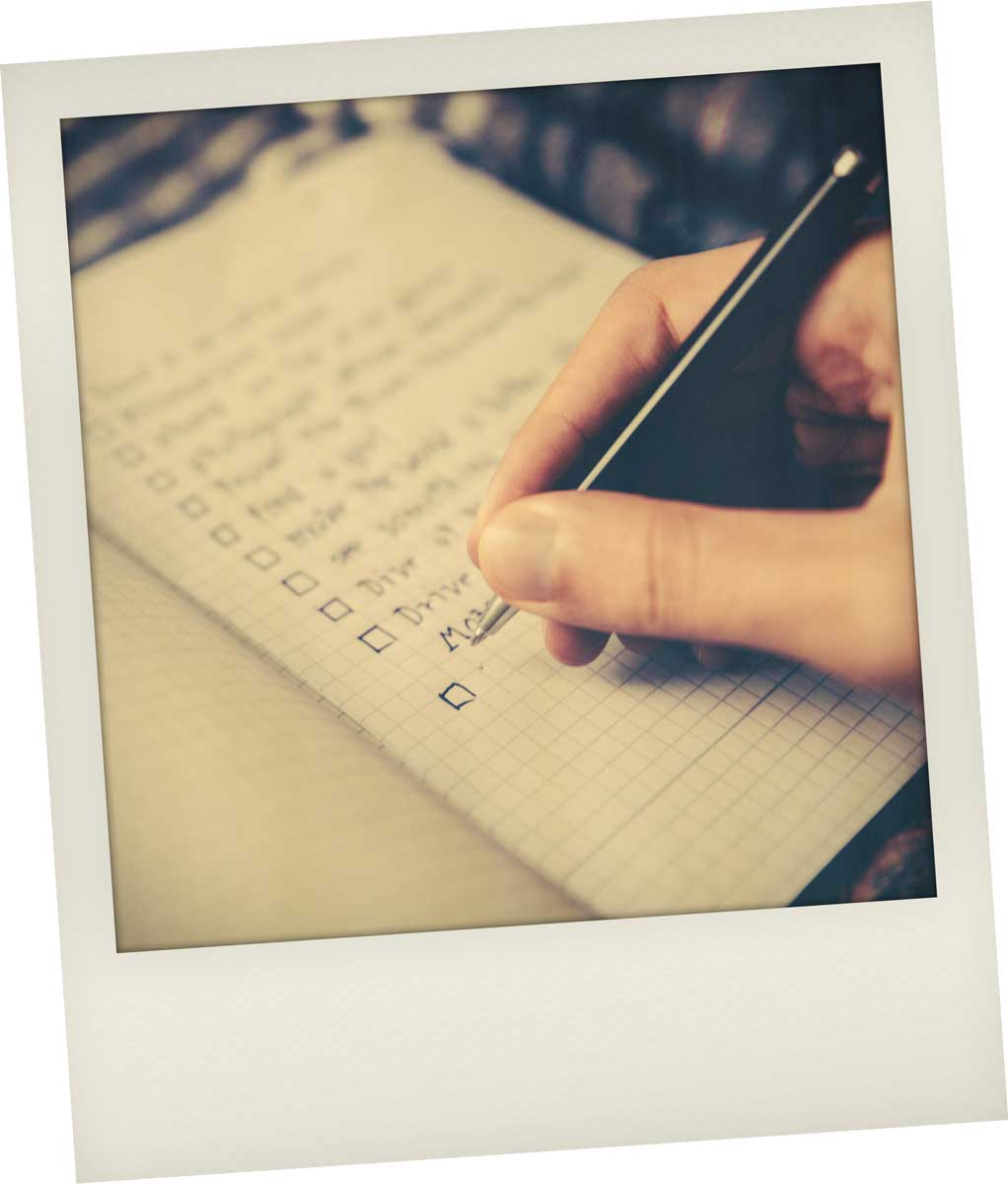 Hand holding a pen and writing on note paper