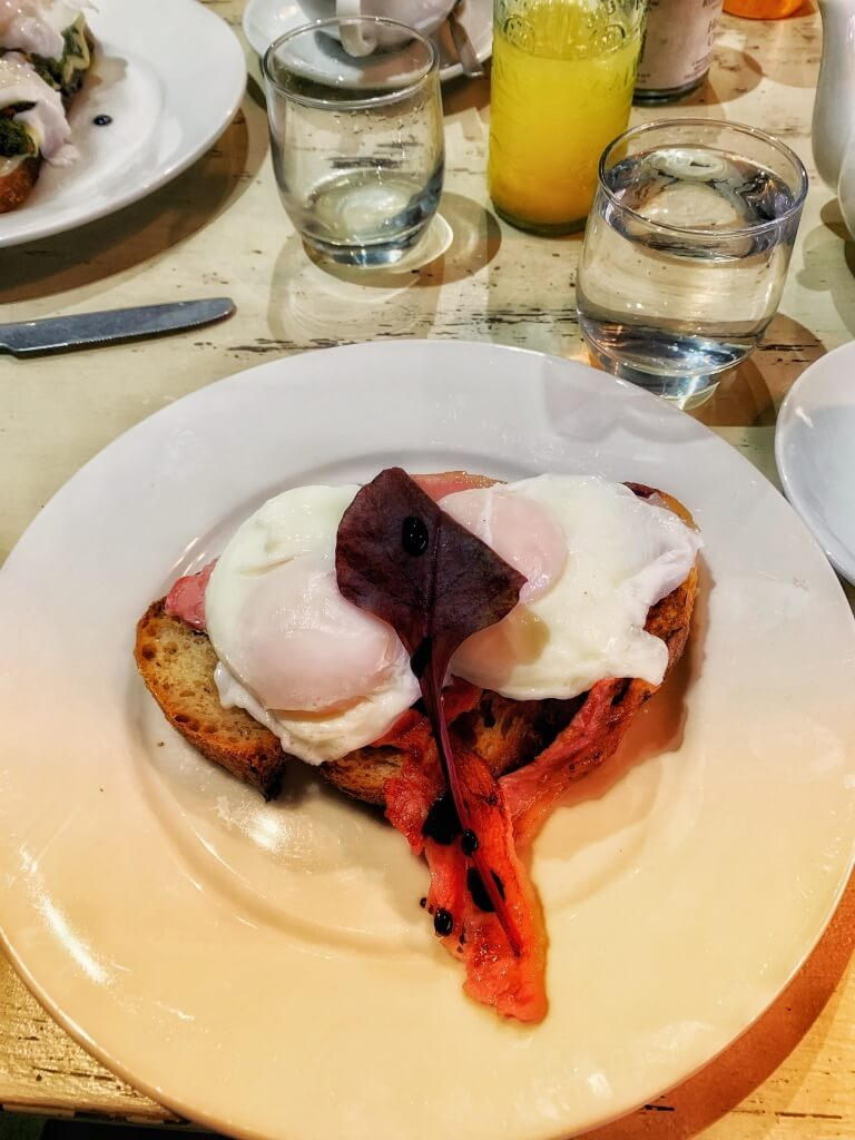 Eggs Benedict on a distressed white table at Bogetta Cafe, York