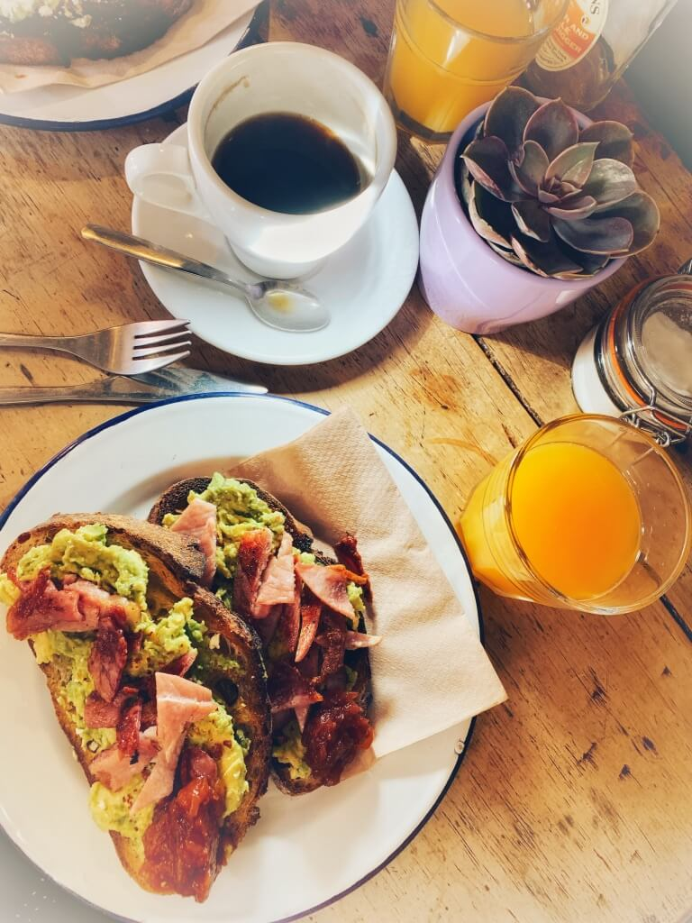 Flat lay photo of smashed avocado on toast with bacon, black coffee and orange juice