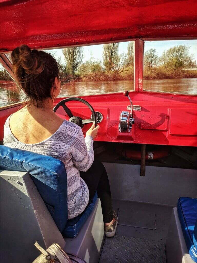 Helen driving a little red boat on the River Ouse