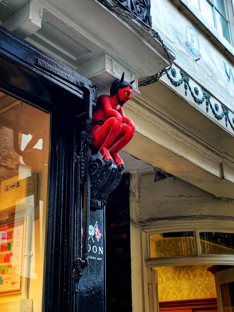 little red devil above a shop in York