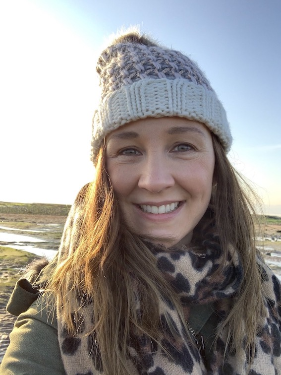 A girl with long brown hair wearing a bobble hat on a beach in winter