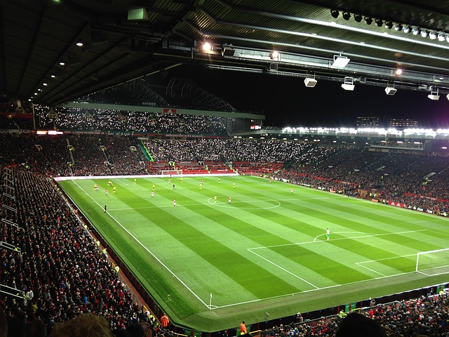 Manchester United Football Ground, Old Trafford, lit up in floodlights. One of the fun things to do in Manchester is to take a tour around the Old Trafford Football Ground