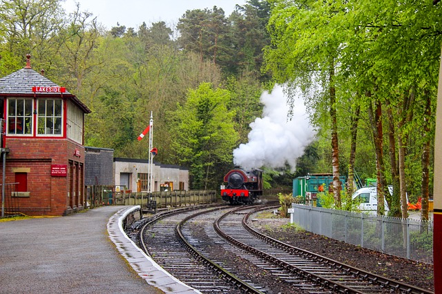 steam train coming into haverthwaite train station in the lake district