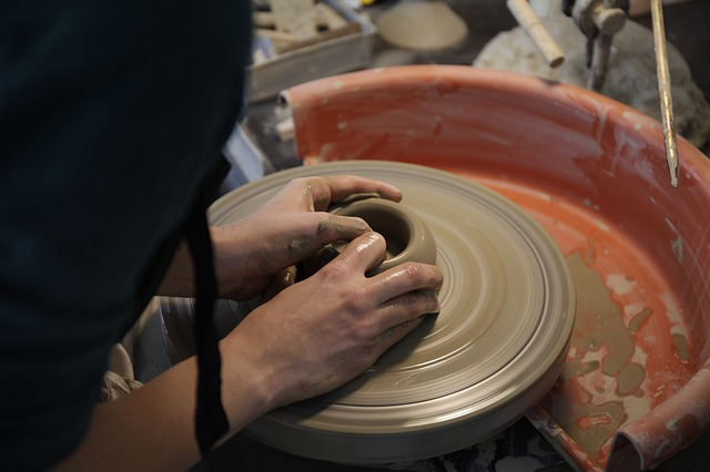 hands sculpting a pot on a potters wheel