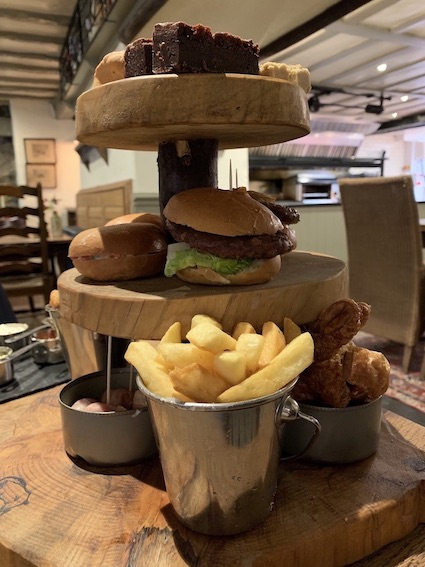 Wild Boar afternoon tea served on tiered tree trunks. On display are chips, mini burgers, chocolate brownie.