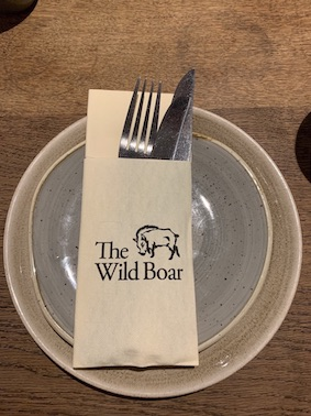 knife, fork and Wild Boar branded napkin set out on a side plate.