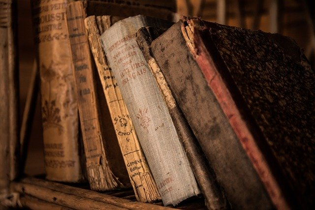 Old, tattered books on a wooden bookshelf