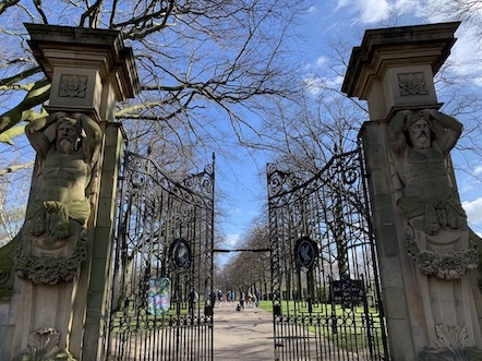 the stone statues and large iron gates at the entrance to Calderstones Park in Liverpool