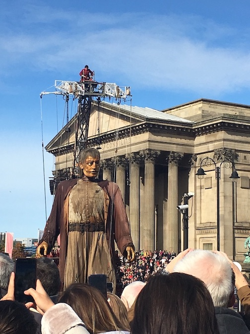 as part of the Giant Spectacular show, one of the many fun things to do in Liverpool, the giant male puppet walks past St. Georges Hall in Liverpool on a sunny day in 2018