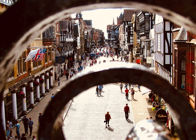 A view of the main shopping street in Chester taken from a high point above the street peeping through some railings