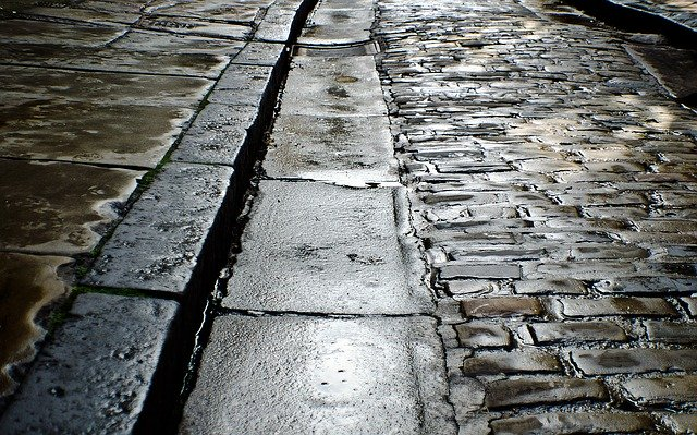 Cobbled road and the roadside curb just after rainfall