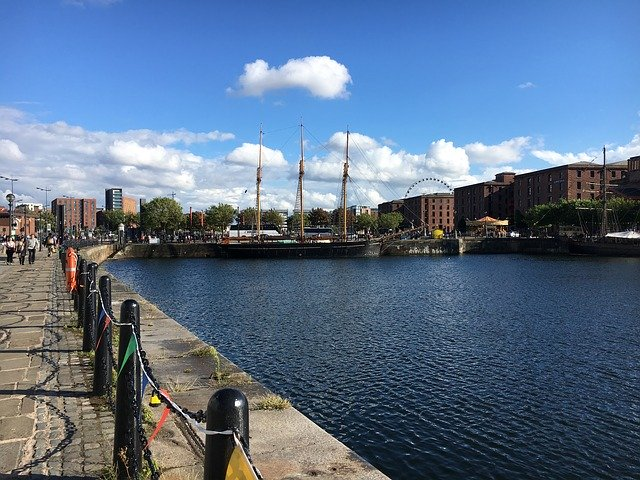 a view of the Albert Dock Liverpool against blue skies with a few white clouds in the sky. There is a tall ship in the background and the top of the Liverpool Ferris Wheel can be seen behind a far building. The dock water and cobbled street is in the foreground