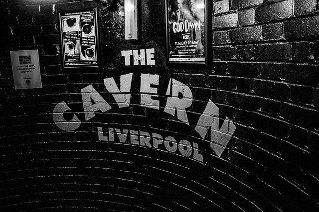 The Cavern Liverpool logo painted in white paint on the black brick wall of the Cavern