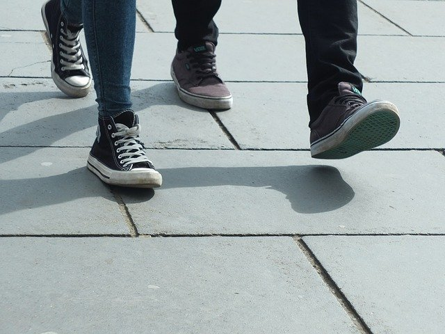 2 pairs of feet, one wearing black Converse High Tops and the other wearing maroon pumps, walking on flagstones