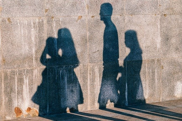 shadows on a wall of 4 people walking together