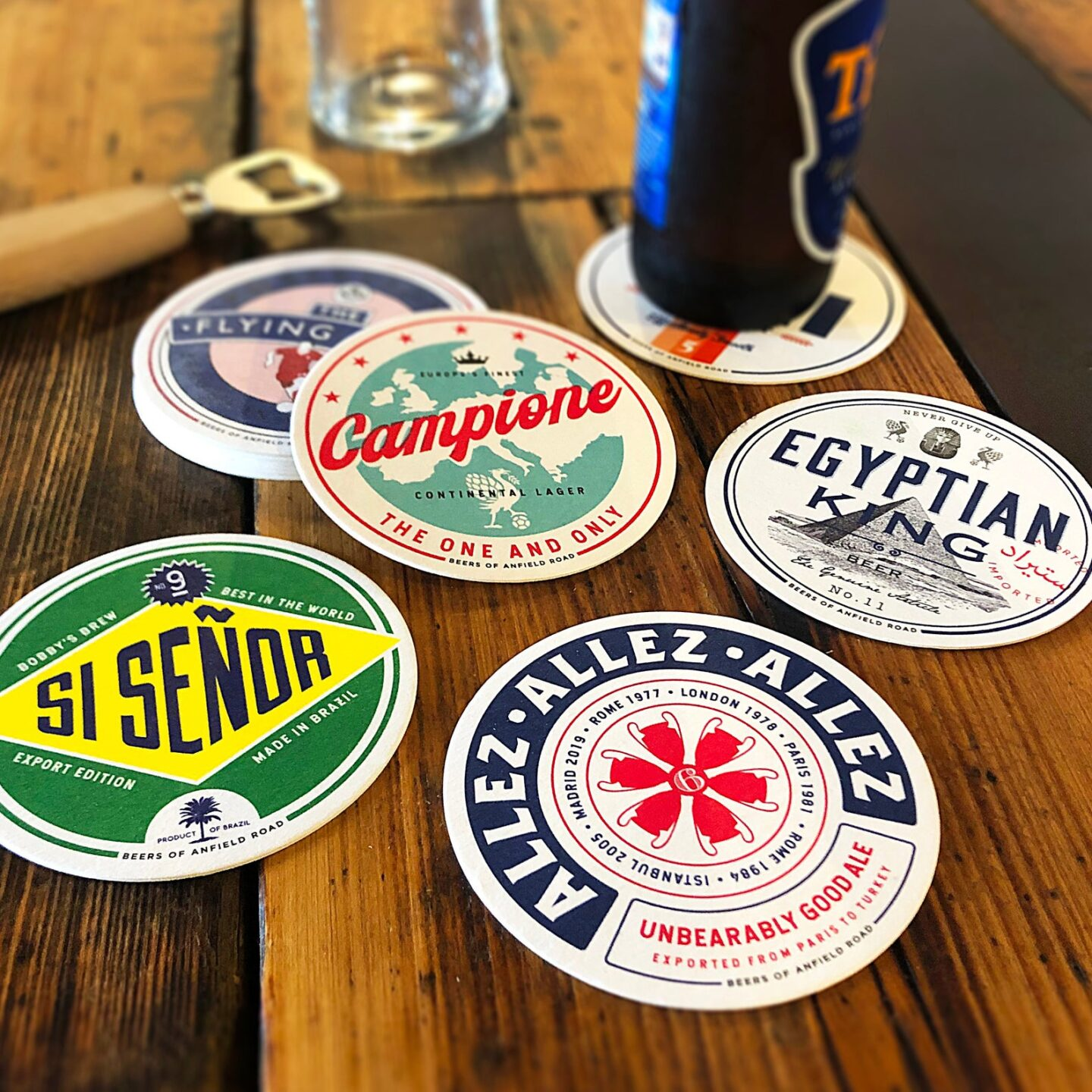 6 Liverpool football club themed beer mats arranged on a wooden table.