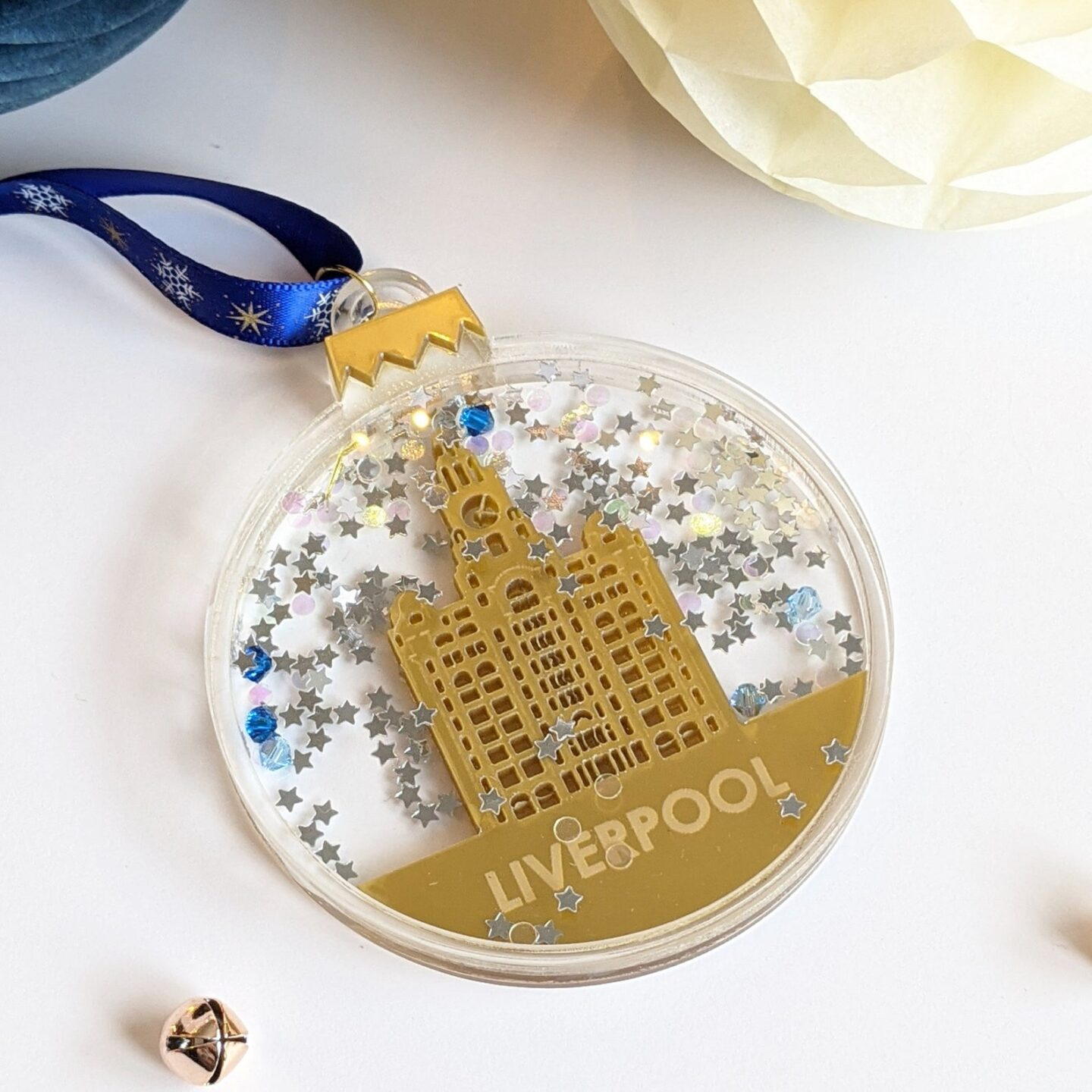 clear perspex flat Christmas tree decoration. Inside the perspex is a gold coloured Liver Building above the words 'Liverpool' engraved into the gold.