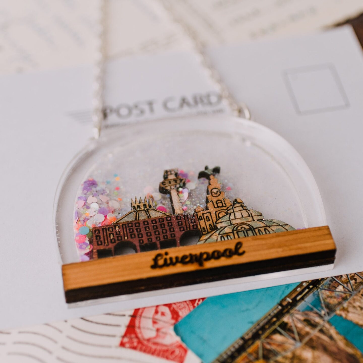 a dome shaped clear perspex pendant on a silver chain. Inside the perspex is a wooden carving of famous Liverpool landmarks sitting atop a piece of wood engraved with the word Liverpool.