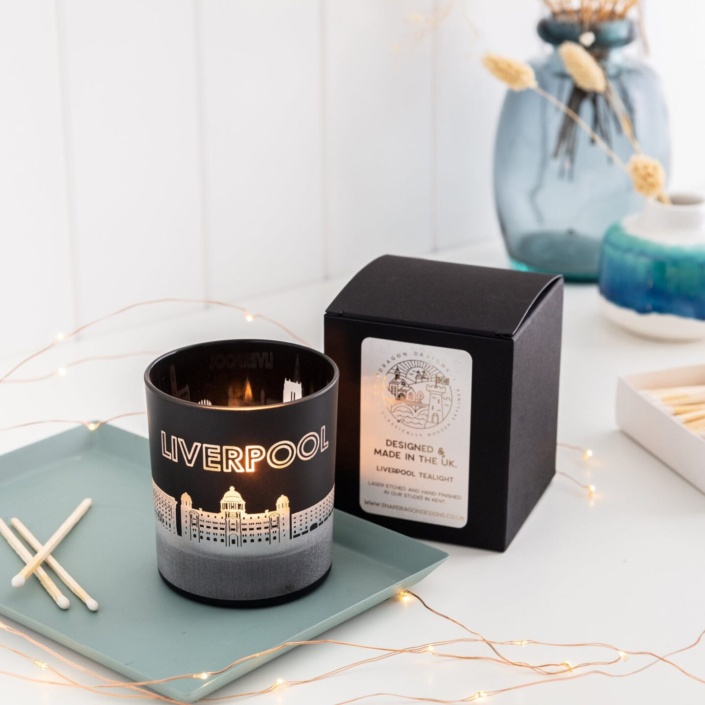 Black coloured Liverpool tea light holder placed in front of the black box it comes packaged within. The tea light holder is shown with a candle burning inside it so that the Liverpool landmarks glow.