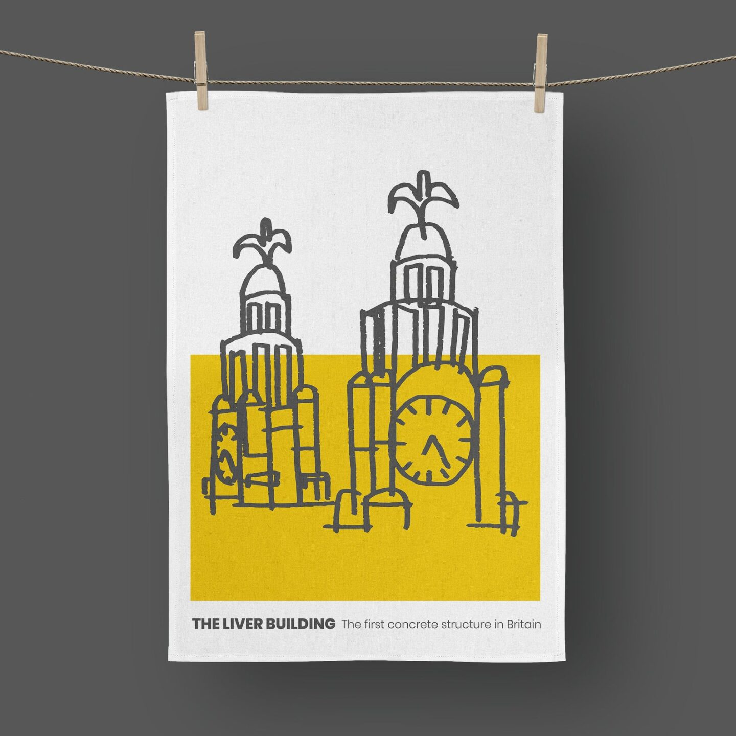 A tea towel with a hand drawn abstract Liver Buildings drawn in grey against a half yellow half white background.