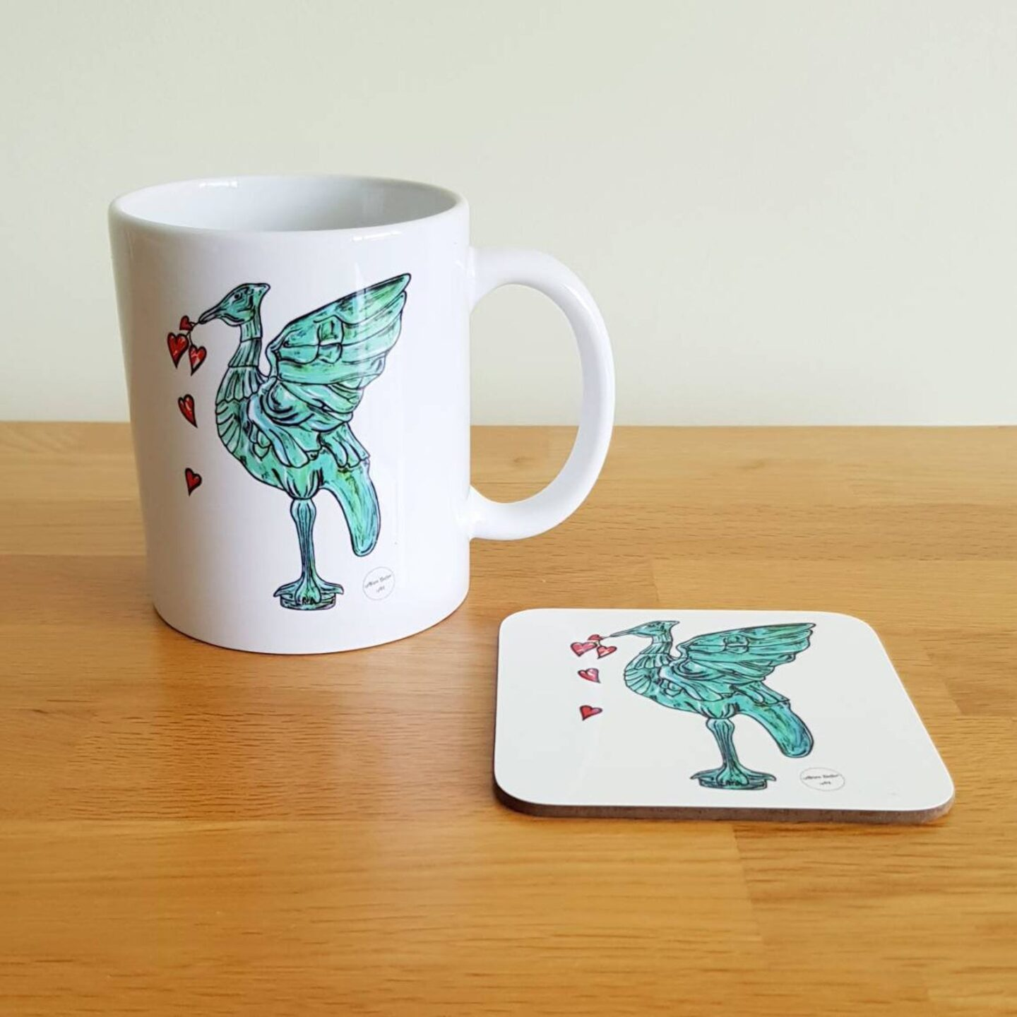 White mug and coaster on a wooden surface. Both have the same hand drawn blue/green coloured Liver Bird with 5 hearts falling from its beak.