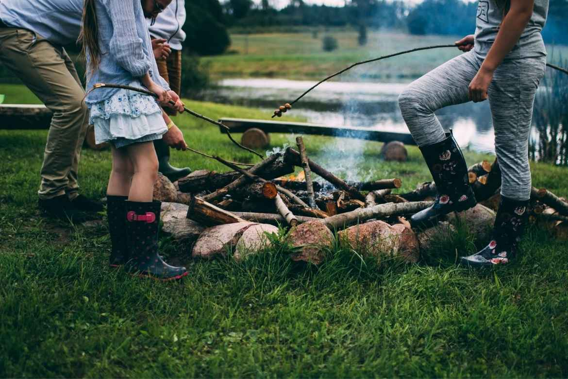 A woman, a man and a girl toasting marshmallows on sticks over a camp fire. Only their legs up to their waists can be seen.