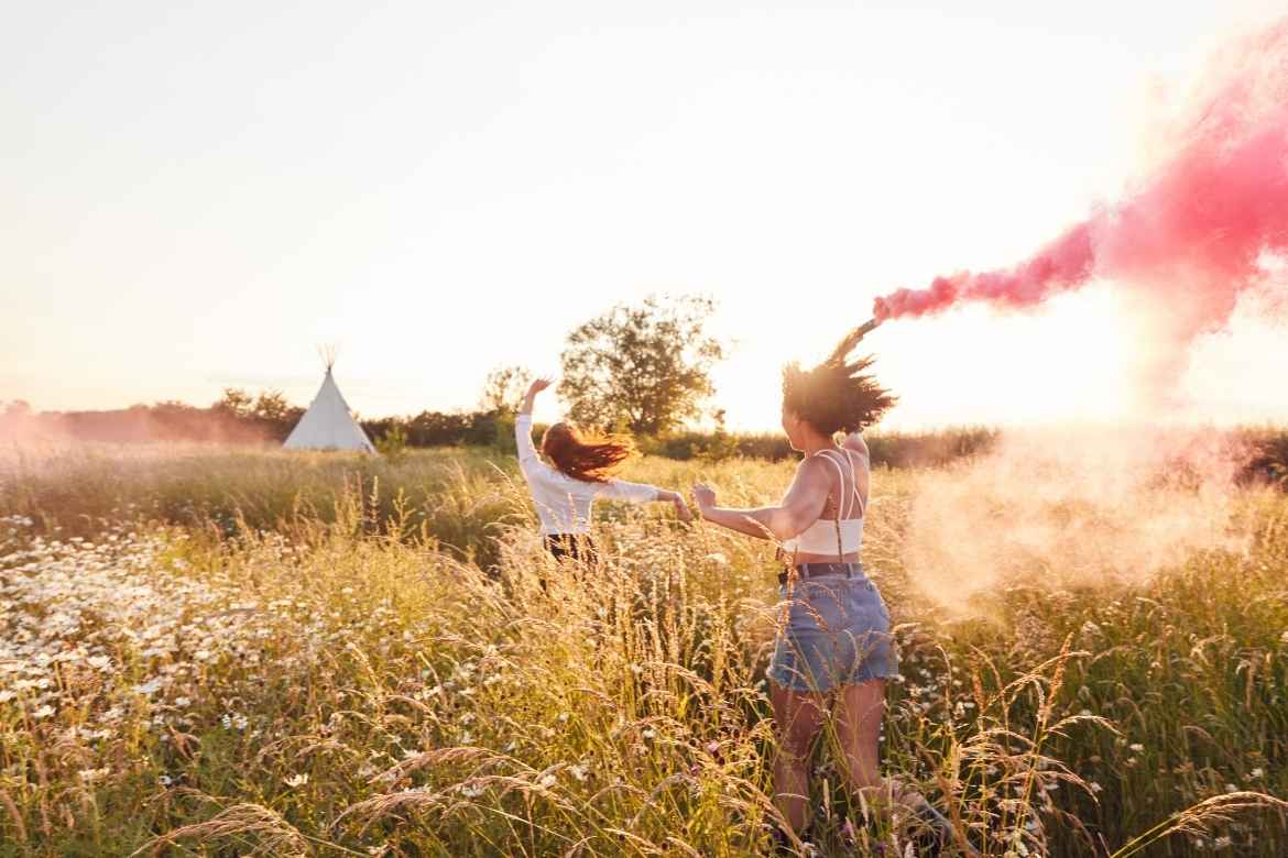 a woman and girl running across a meadow with a pink flare