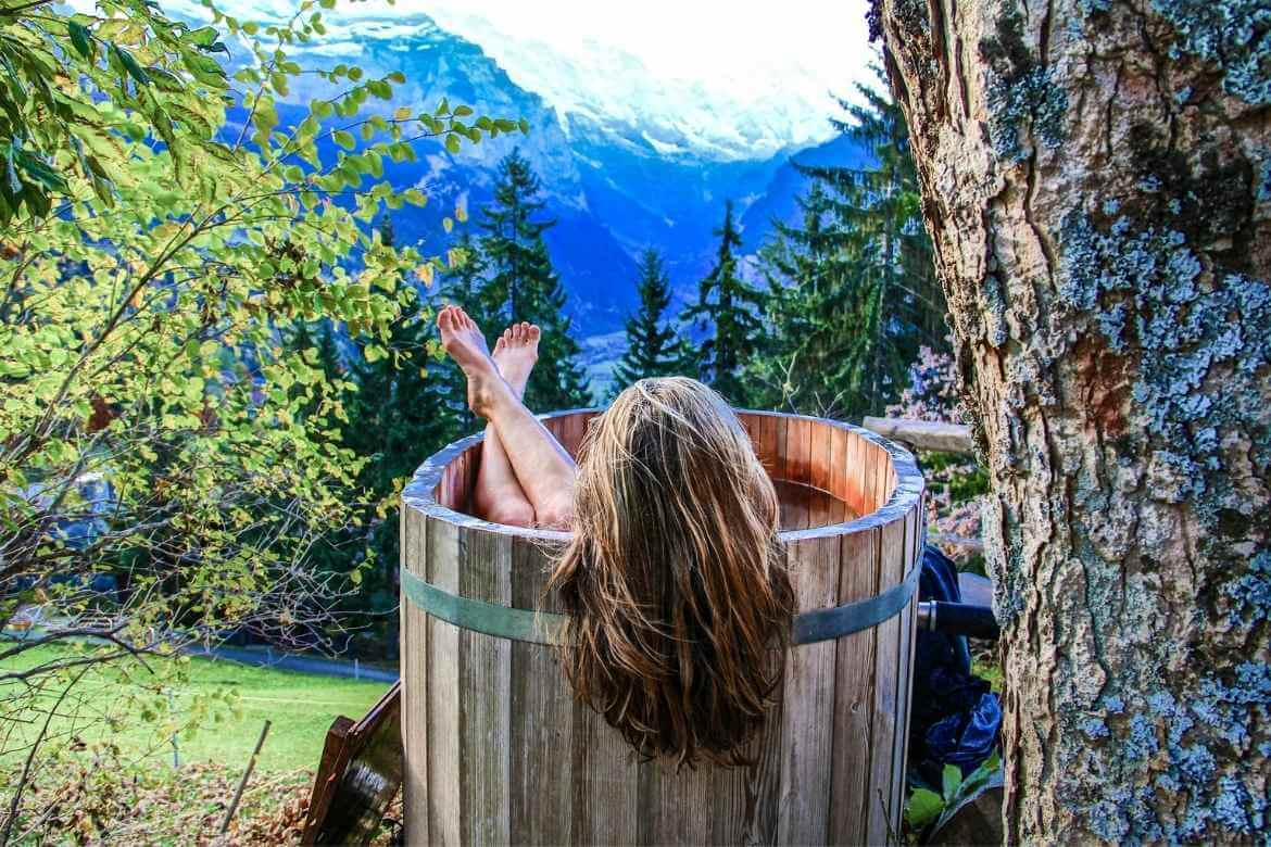 Girl in a barrel hot tub next to a tree looking out onto mountain landscape