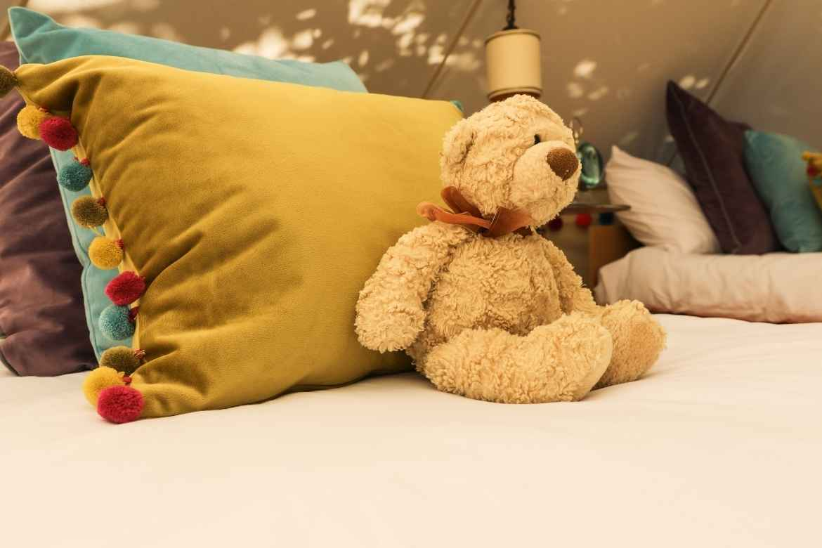 tassled cushions and a teddy bear on a bed in a glamping tent