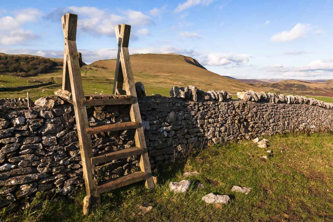 a wooden stile over a limestone drystone wall in Derbyshire Peak District