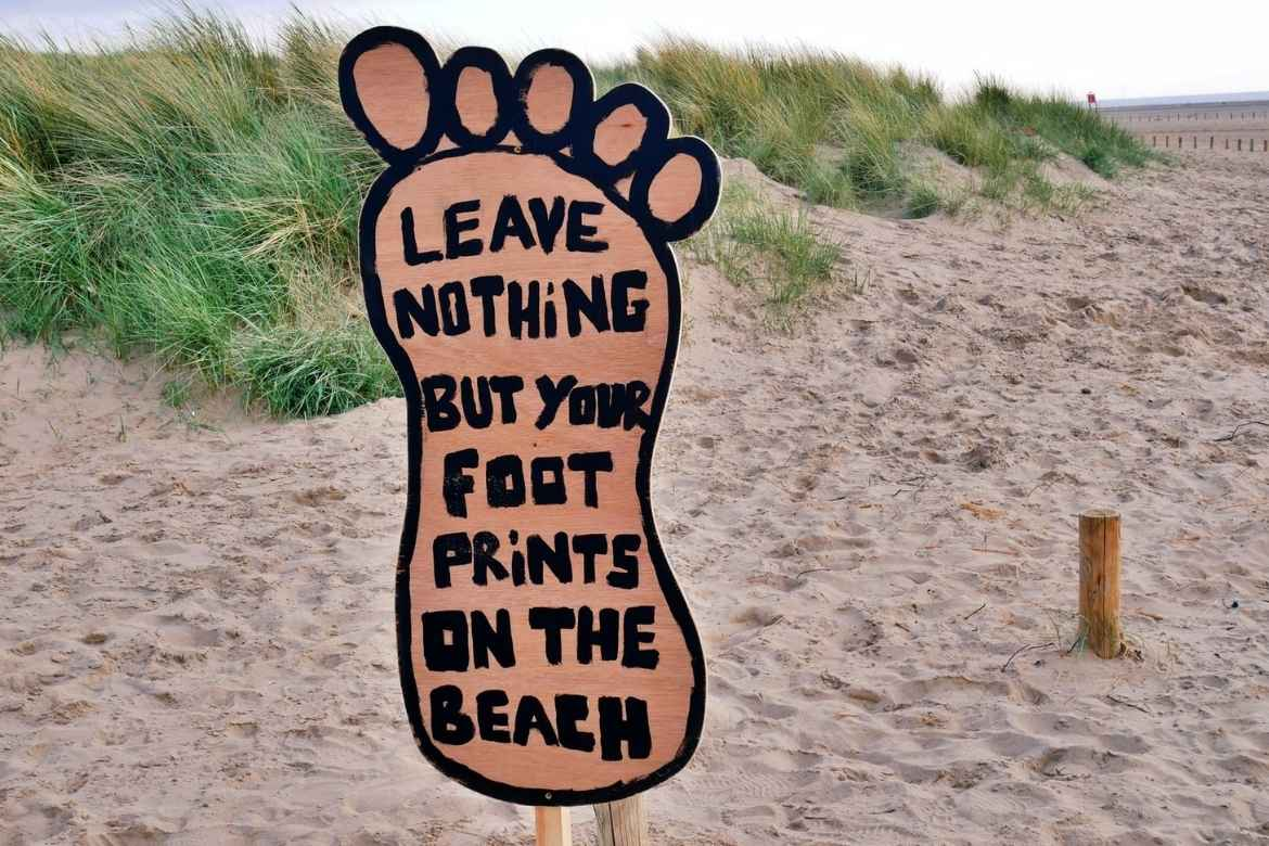 """A large sign on the beach in the shape of a footprint reading """"leave nothing but your foot prints on the beach"""""""