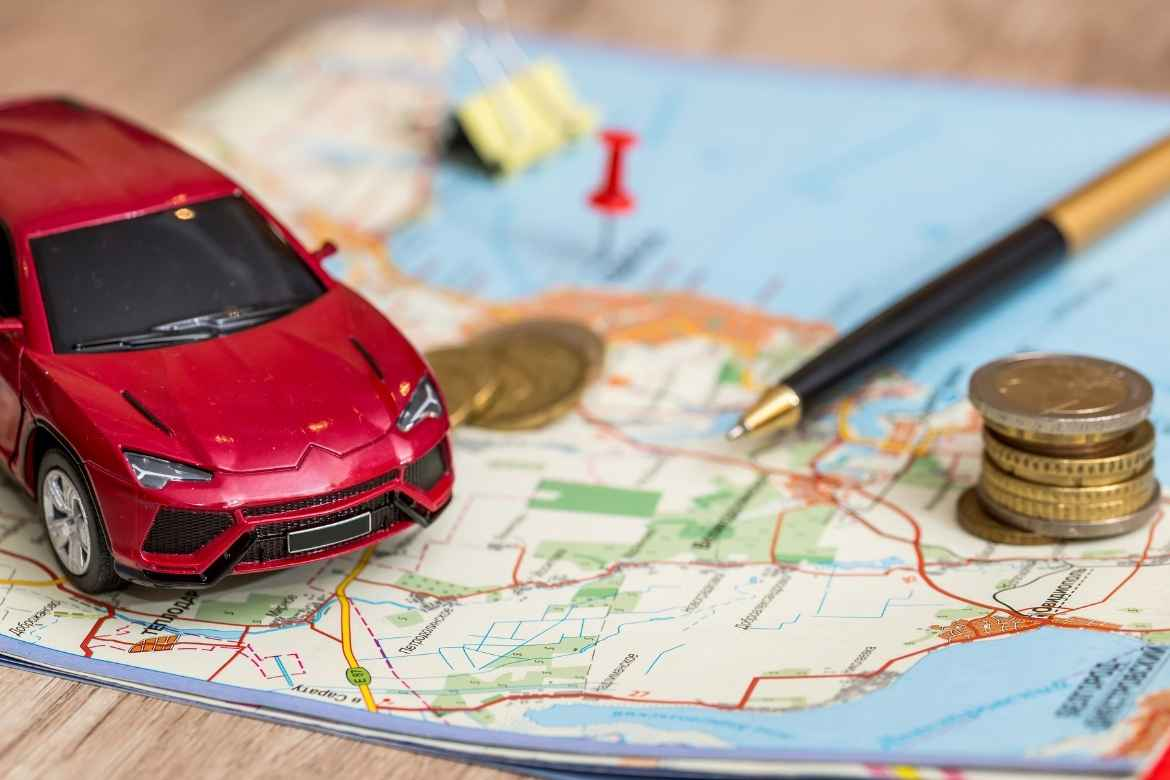 red toy car, a pen and some loose coins on top of a map