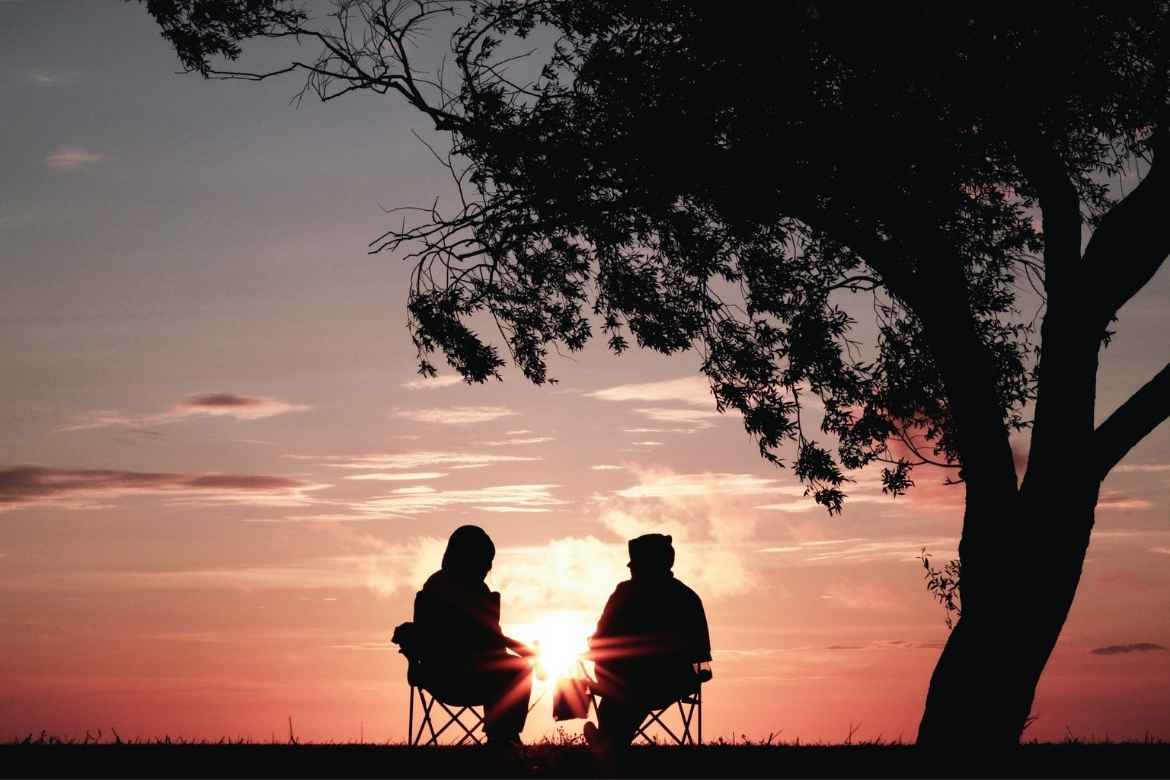 silhouette of a couple sitting on deckchairs under a tree at sunset