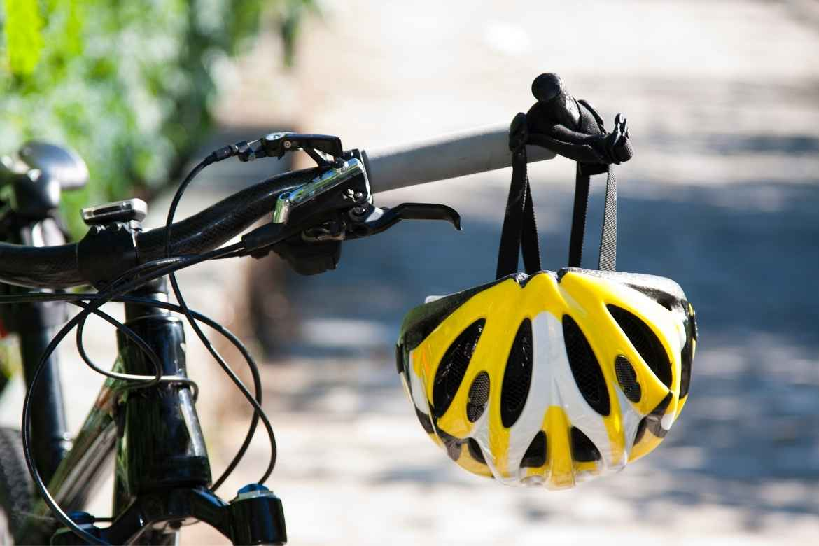 bike handlebars with a yellow and white cycle helmet hanging from the left handle bar