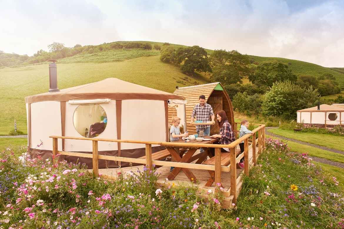 a mum and son sitting at a table in front of a glamping tent whilst the dad carries a tray of food