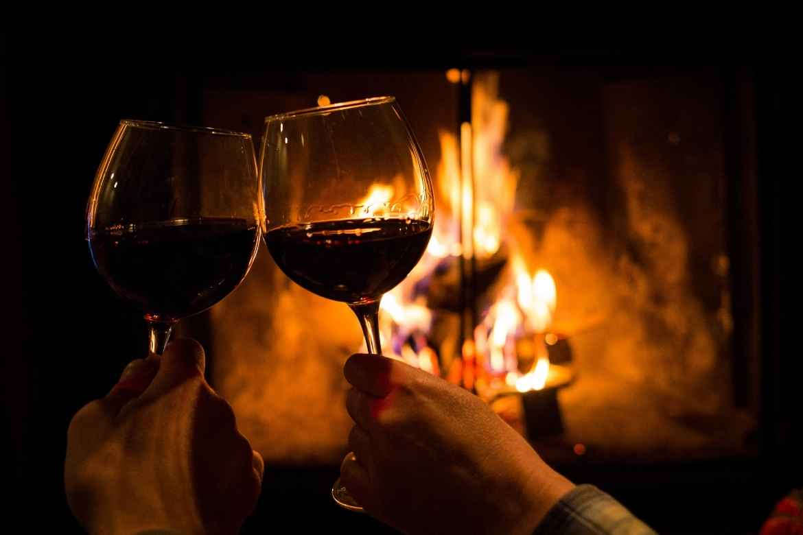 two hands holding wine glasses filled with red wine, brought together in a 'cheers' motion with the backdrop of a roaring fire pit