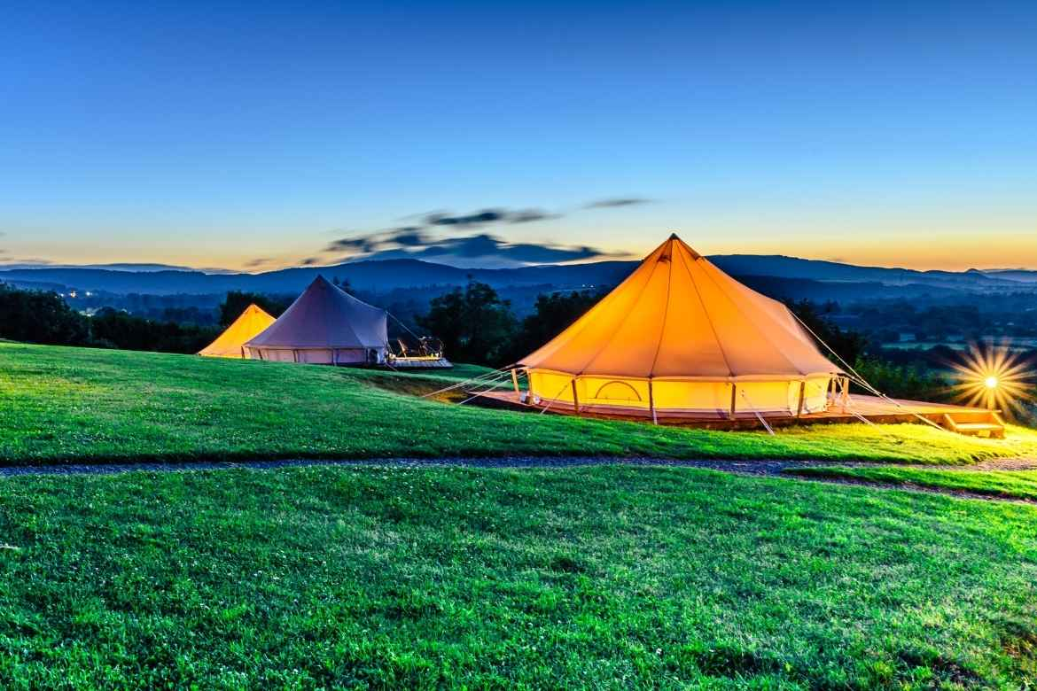 a field of glamping bell tents lit up in the dark night