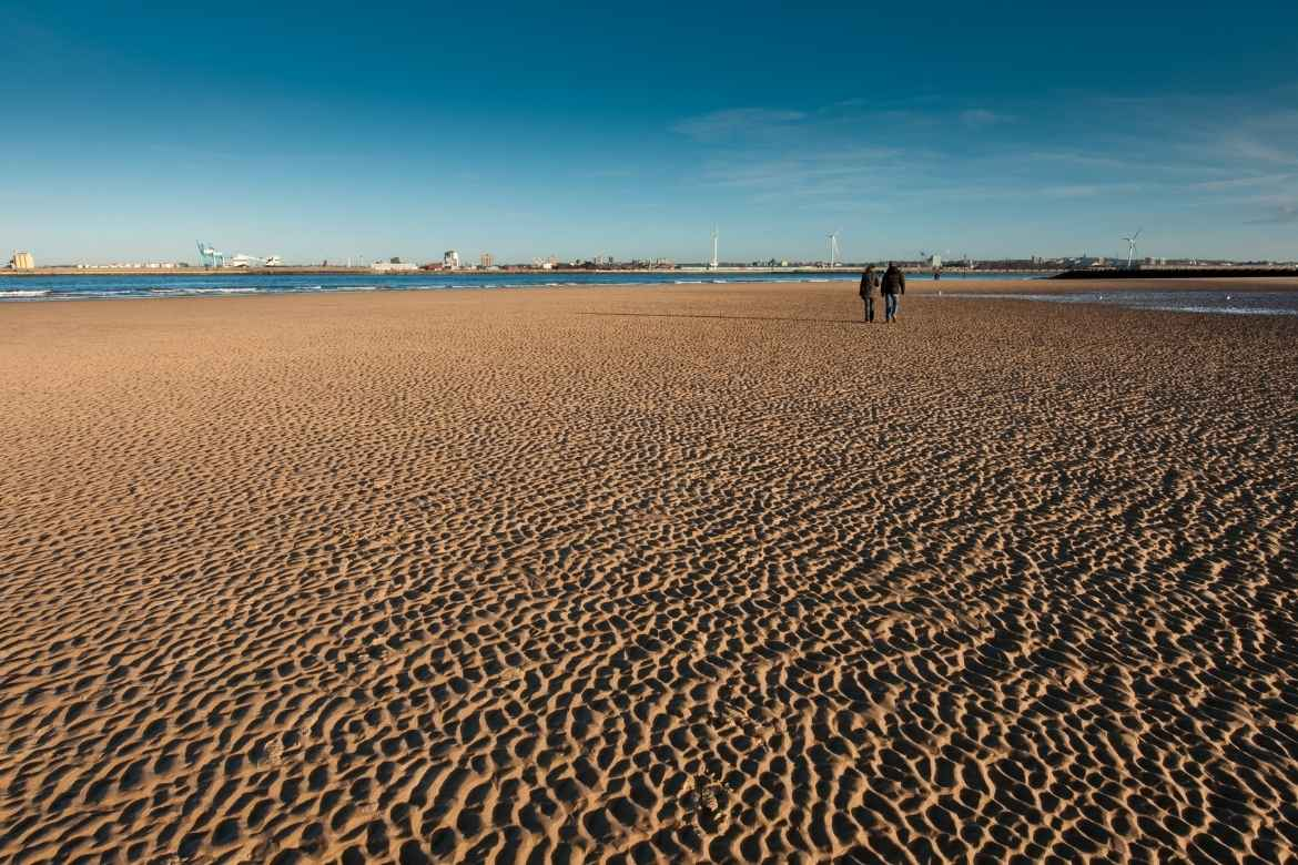 two people walking on new brighton beach with buildings of liverpool in the distance