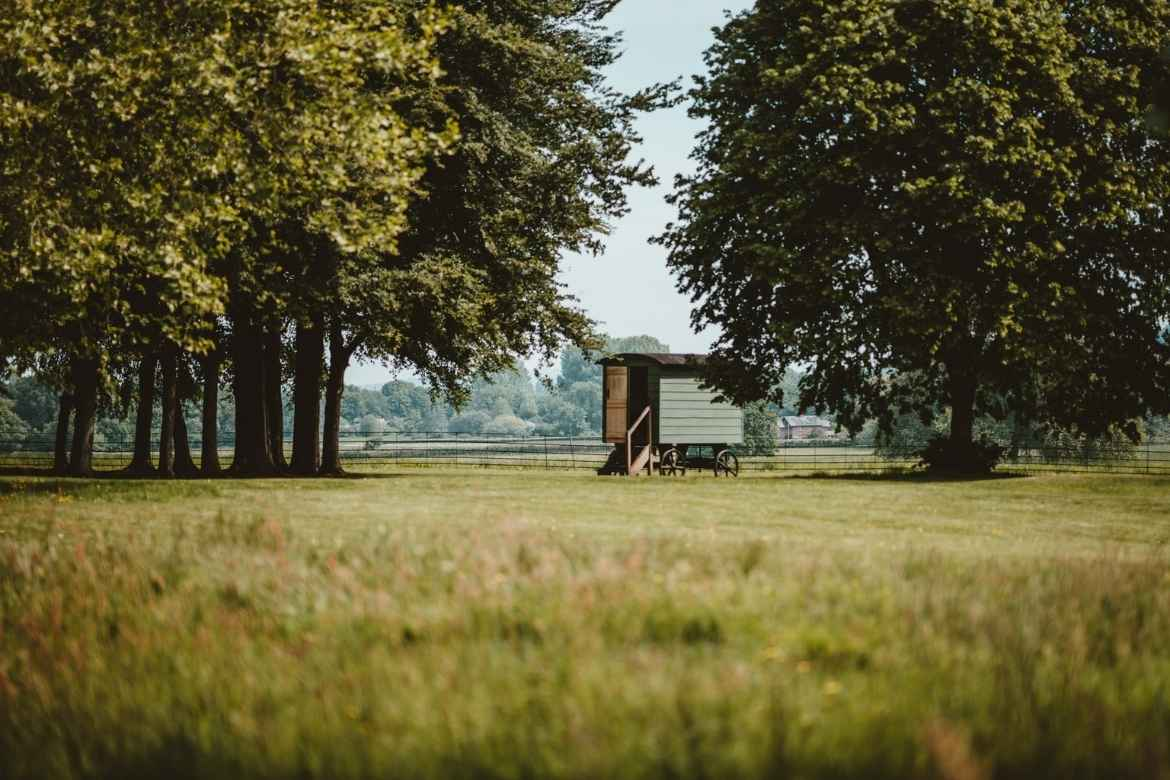 shepherds hut in a field surrounded by trees