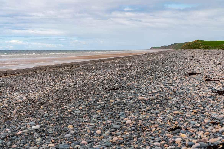 stoney Silecroft beach with grassy hills