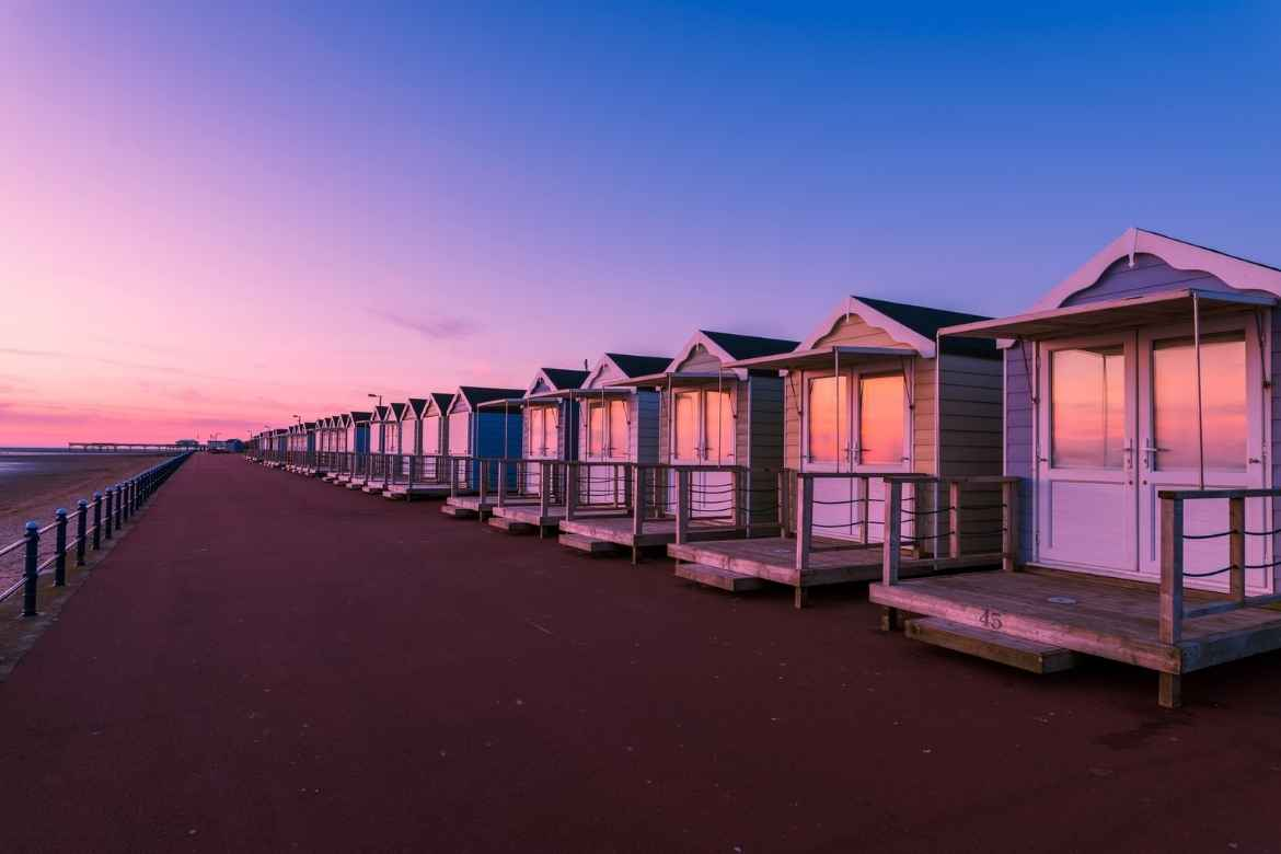 row of beach huts on the beach front at St Annes Beach