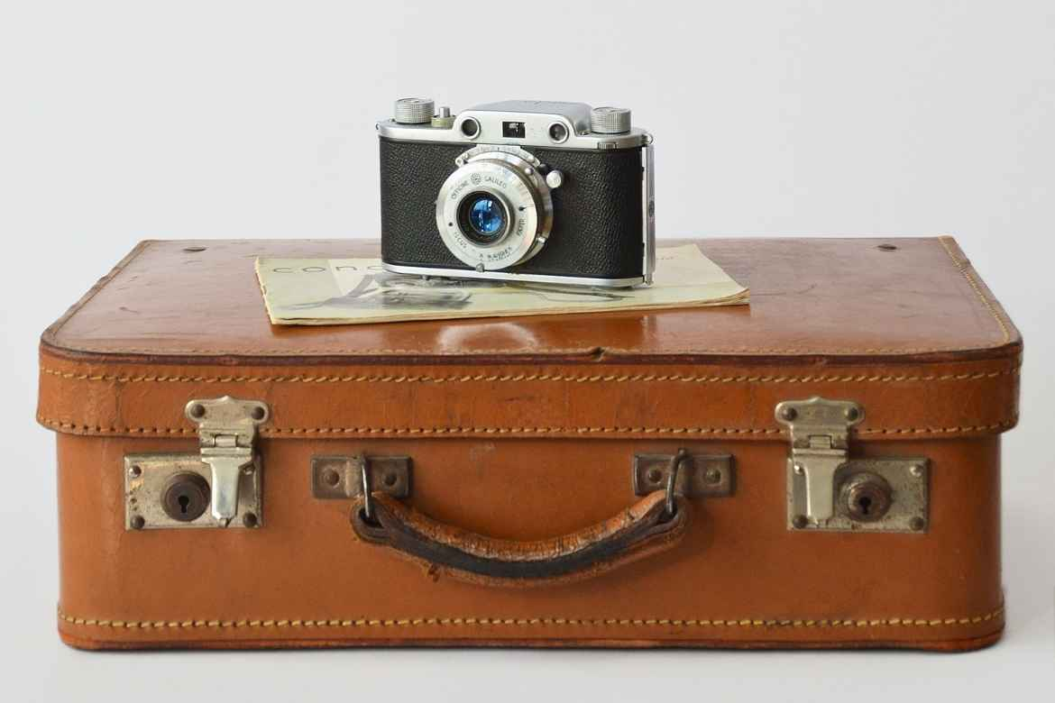 an old fashioned tan leather suitcase with a vintage camera set on top