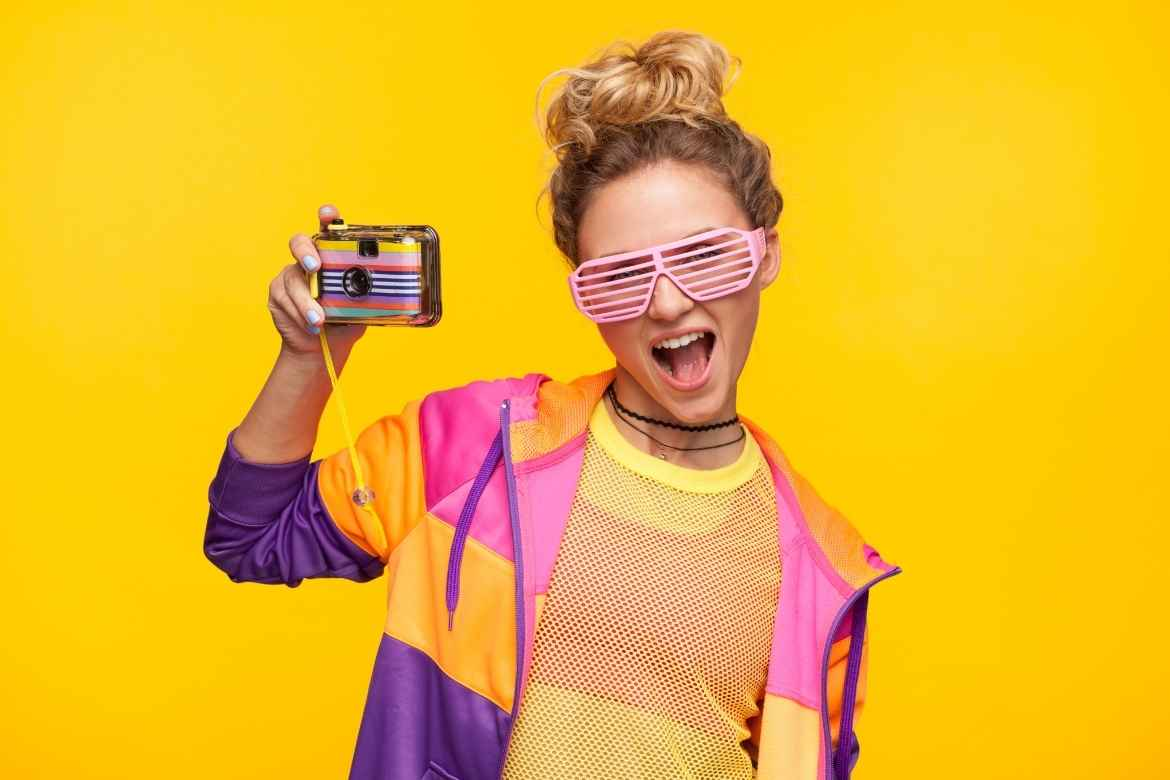 teenage girl with blonde hair, pink glasses and bright coloured clothing holds up a colourful kids action camera against a bright yellow background