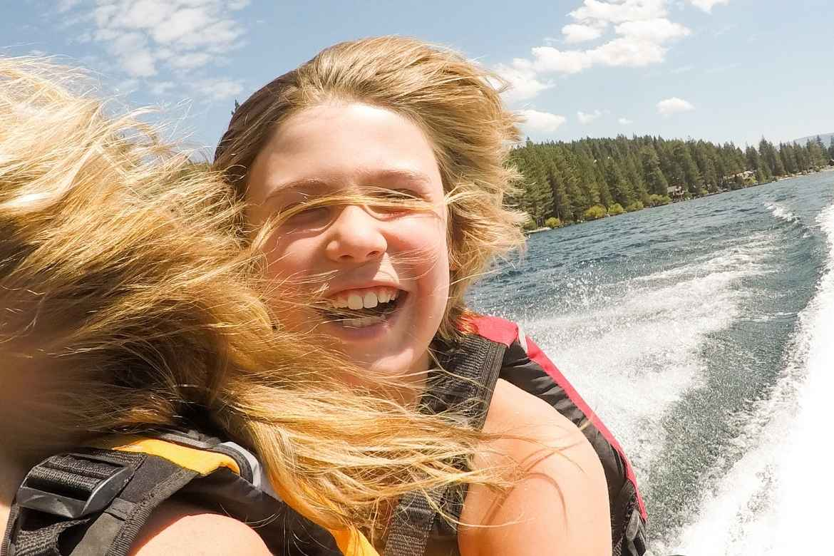 photo taken by a kid with an action camera on the back of a jet ski with mum's blonde hair blowing in his face